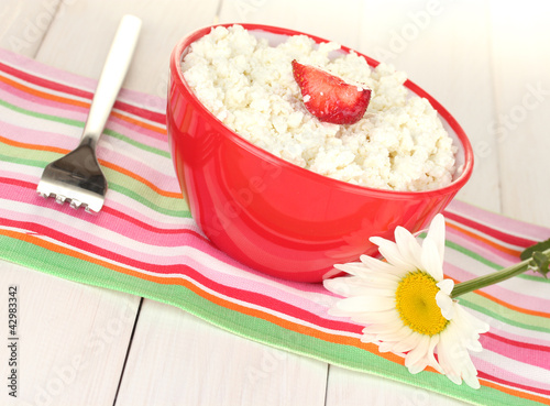 cottage cheese with strawberry in red bowl, fork and flower