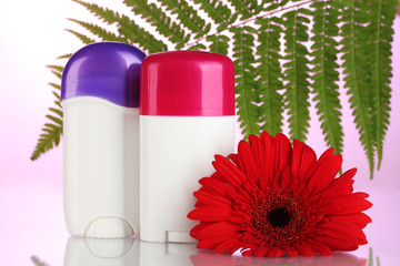 deodorants with flower and green leaf on pink background