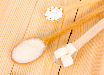 Sweetener and white sugar in spoons on wooden background