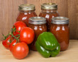 Tomato sauce in jars with tomatoes and peppers