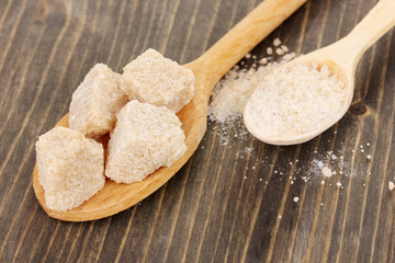 Brown sugar in spoons on wooden background