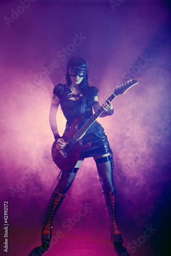 Goth girl in goggles plays guitar