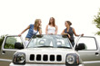Three women posing on a car