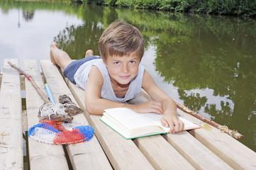 Kind liest auf Steg