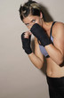 Muscular woman practising boxing