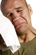 Man wiping his tears with a tissue
