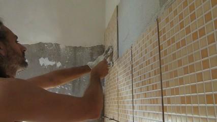tiler at work gluing  mosaic tiles
