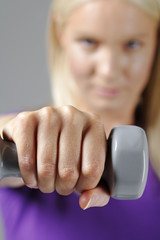 Young woman using fitness weights