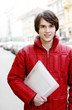 Man in red jacket holding a file