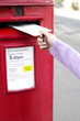 Hand putting a letter into the post box