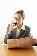 Businesswoman drinking wine while reading newspaper