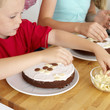 Boy and girl decorating cakes with chocolate candies