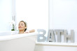 Woman listening to music while resting in bathtub