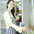 Woman smiling at the camera while holding the refrigerator door