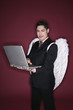 Businessman with angel wings using laptop