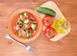 Fresh salad with tomatoes and cucumbers on wooden background