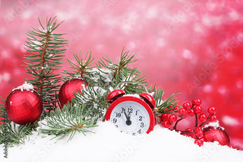 Green Christmas tree with toy and clock in the snow on red