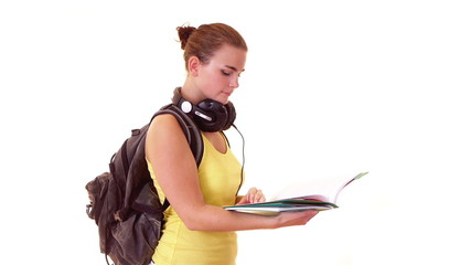 schoolgirl with headphones and backpack reading something