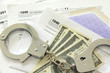 Tax papers with dollar bills and handcuffs