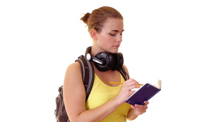 student with headphones and backpack writing note