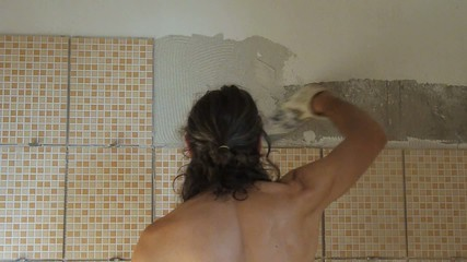 tiler spreading tile glue on a wall
