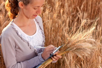 Woman agronomist writes results of his experiment in the wheat