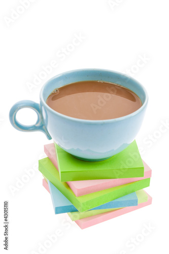 Cup of coffee on a stack of adhesive notepads