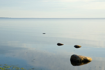 Calm and bright water with stones