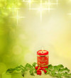 Christmas candle and evergreen against bokeh background