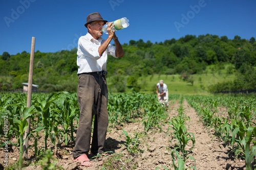 Old rural worker drinking water outdoor
