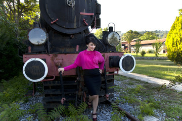 Young beautiful woman looking through from locomotive
