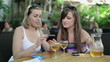 Female friends with smartphone in outdoor bar