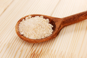 Brown sugar in spoon on wooden background