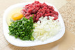 Chopped onion, minced beef, parsley and an egg on plate