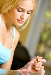 Young beautiful woman making manicure, indoors