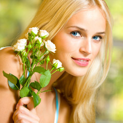 Cheerful woman with bouquet of white roses