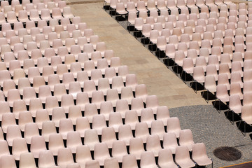 Many rosa chairs lined up for concert or speach