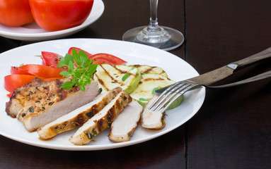 Pork steak with grilled zucchini and tomato salad