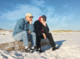 Two Bored Retired Men Sitting Together at the Beach