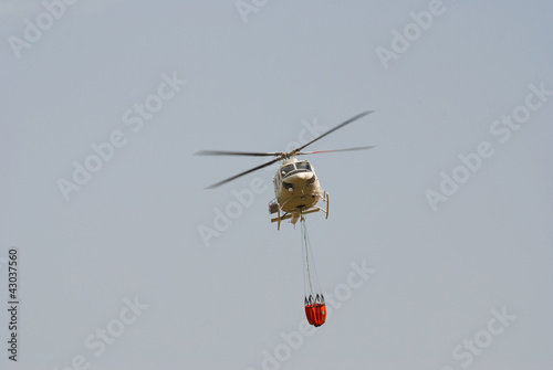 Firefighter helicopter carrying a water bucket