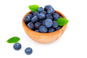 fresh blueberry in a wooden bowl with leaves, over a white backg