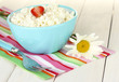 cottage cheese with strawberry in blue bowl, fork and flower