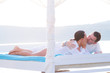 Couple lying on luxury white bed at the sea