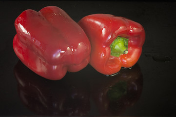 Two red peppers on black background