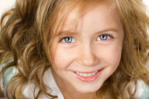 close-up portrait big smiling little girl wiht blue eyes