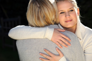 A woman and her daughter hugging.