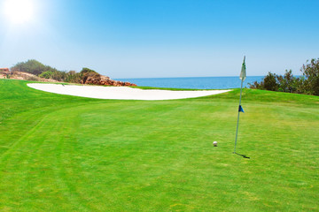 Golf green field on the background of the sea. In the summer in