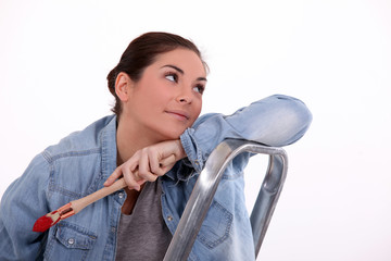 Dreamy woman taking a break from painting