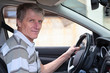 Experienced driver mature male holds steering wheel in own car