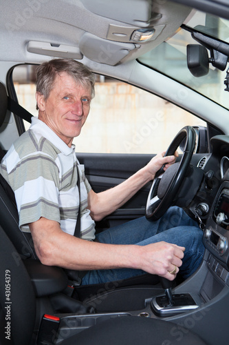 Experienced driver mature Caucasian man sitting inside of car